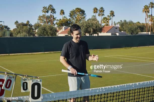 mixed race man bounces tennis ball on racket strings on grass court - racquet stock pictures, royalty-free photos & images