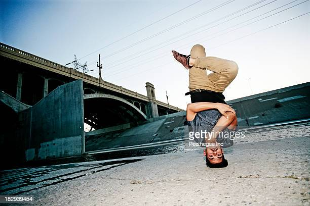 mixed race man break dancing under overpass - breakdancing stock photos and pictures