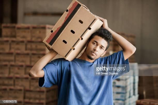 Mixed race man carrying cardboard box in warehouse
