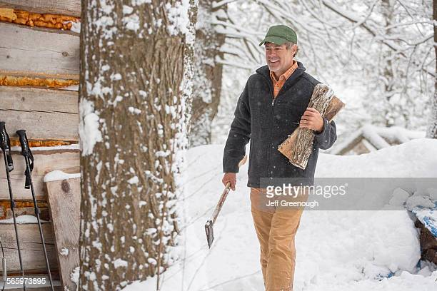 Mixed race man carrying firewood in snow