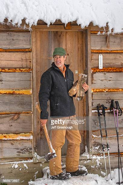 mixed race man carrying firewood near snowy shed - ski pole stock pictures, royalty-free photos & images