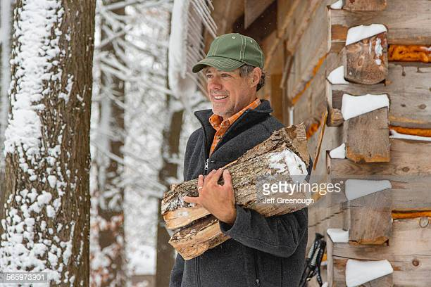 Mixed race man carrying firewood near snowy shed