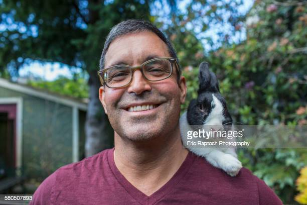 Mixed race man carrying rabbit on shoulder