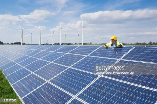 mixed race man checking solar panels - solar energy stock pictures, royalty-free photos & images