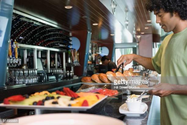 Mixed race man choosing food from breakfast buffet