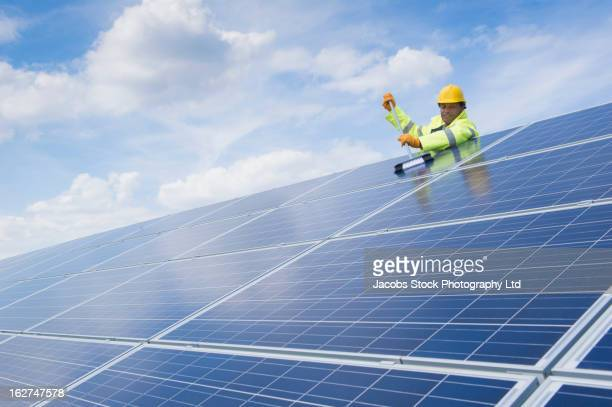 Mixed race man cleaning solar panels
