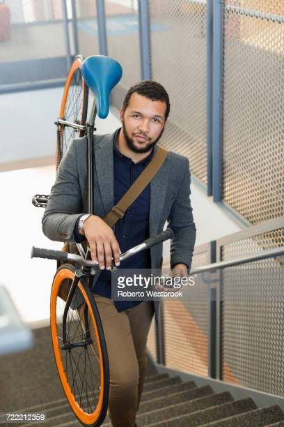 Mixed Race man climbing staircase carrying bicycle