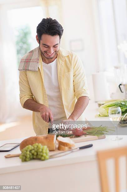 mixed race man cooking in kitchen - 根菜 ストックフォトと画像