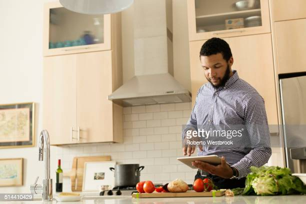 Mixed race man cooking with tablet computer in kitchen