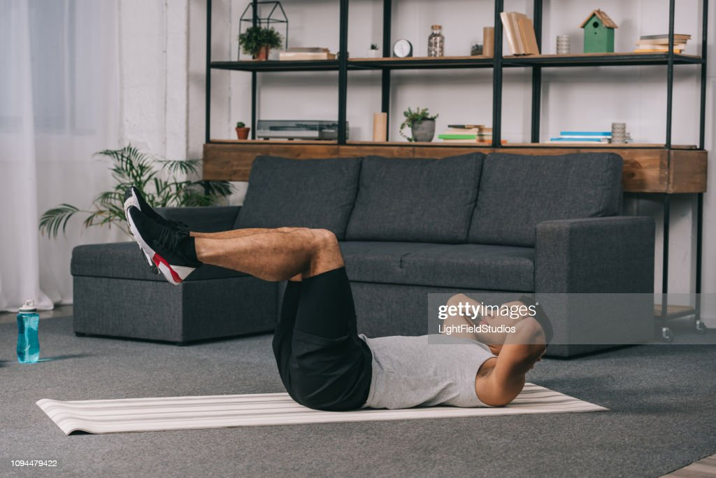 mixed race man doing exercise on fitness mat in living room : Stock Photo