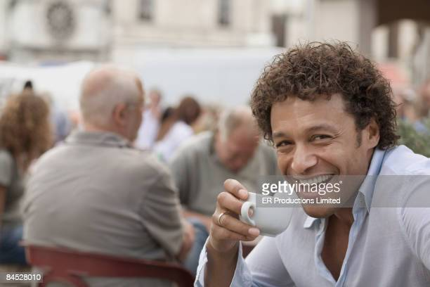 mixed race man drinking coffee at sidewalk cafe - midi pyrénées stock photos and pictures