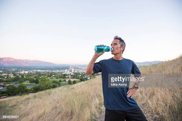 Mixed race man drinking water bottle on hilltop