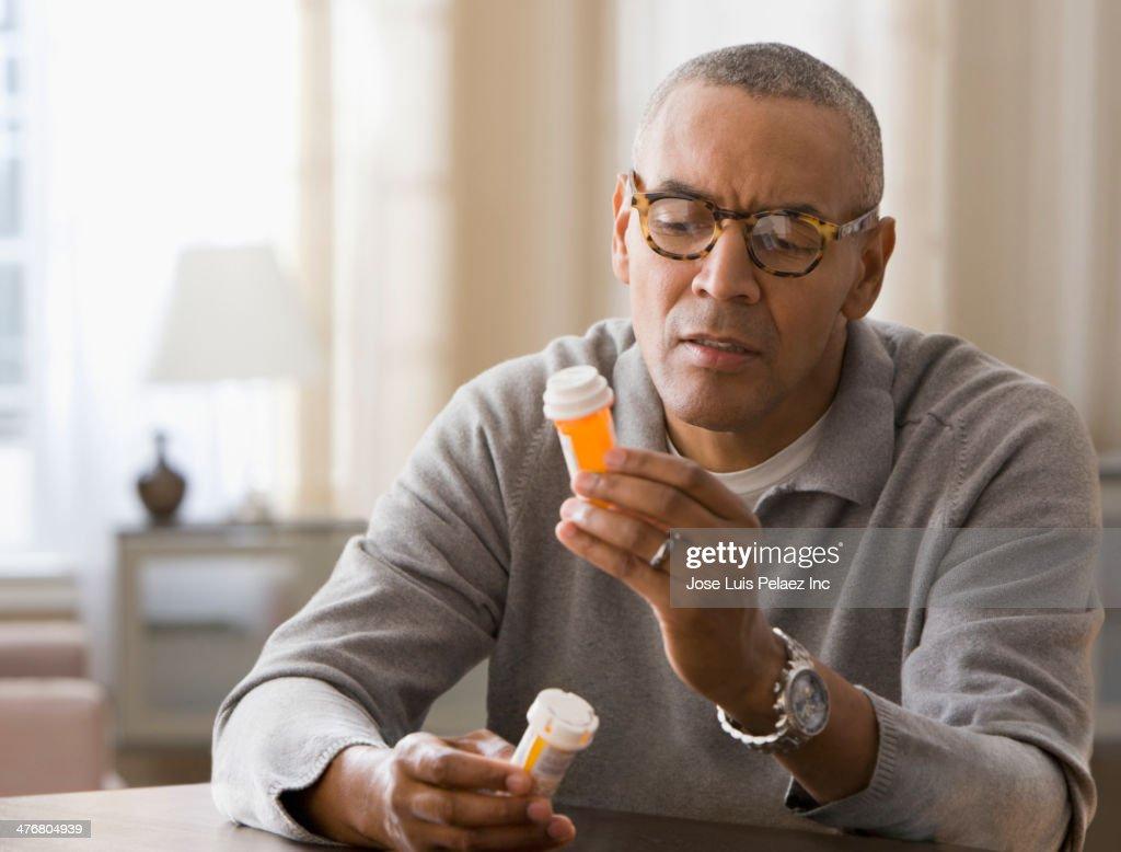 Mixed race man examining prescription bottles : Stock Photo