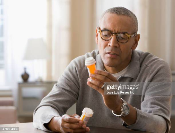 Mixed race man examining prescription bottles