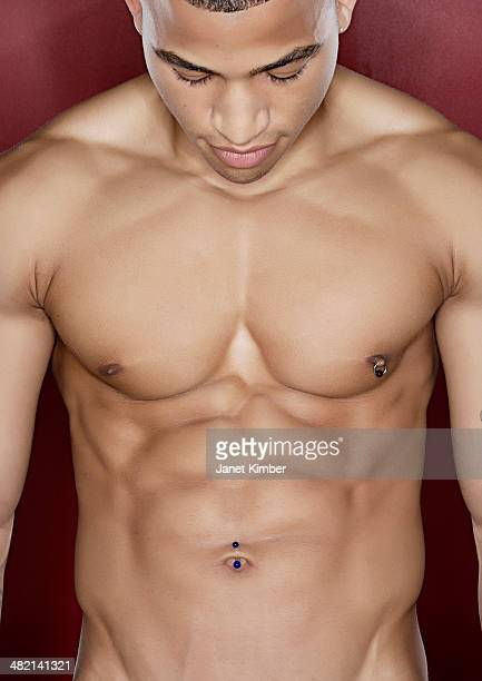 mixed race man flexing abdominal muscles - brustwarzen piercing stock-fotos und bilder