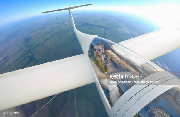 Mixed race man flying glider airplane