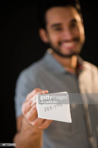 mixed race man giving out phone number on napkin - telephone number stock pictures, royalty-free photos & images