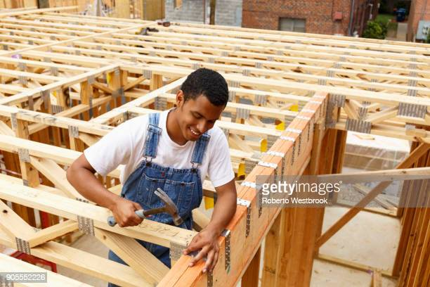 Mixed race man hammering nail at construction site