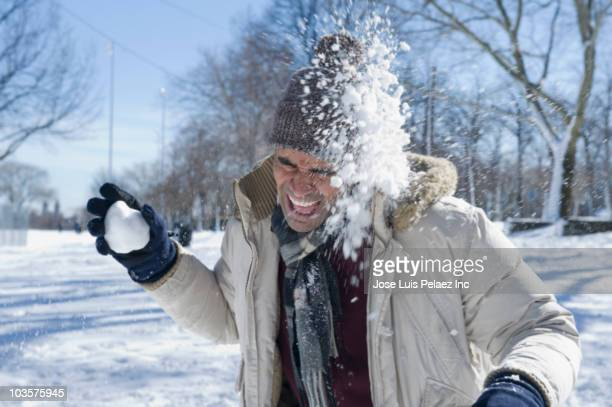 Mixed race man having snowball fight