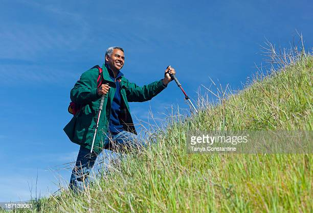 Mixed race man hiking on grassy hill