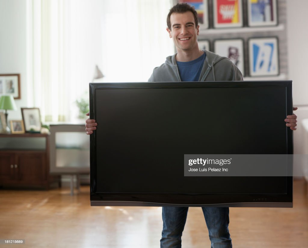 Mixed race man holding big screen television : Stock Photo