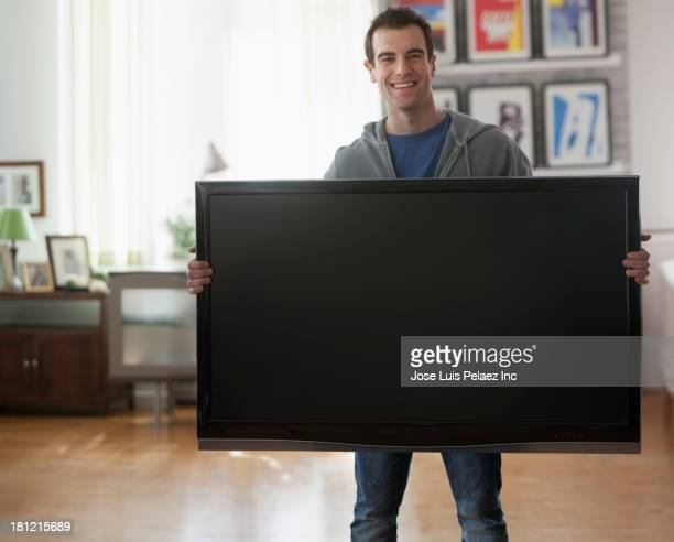 Mixed race man holding big screen television