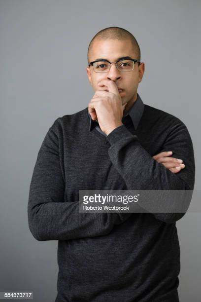 mixed race man holding chin in hand - あご ストックフォトと画像