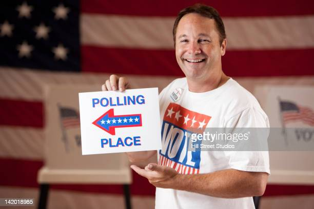 mixed race man holding direction sign in polling place - gardena california stock pictures, royalty-free photos & images