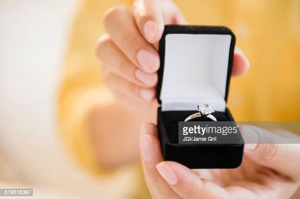 mixed race man holding engagement ring in box - engagement ring box stock photos and pictures