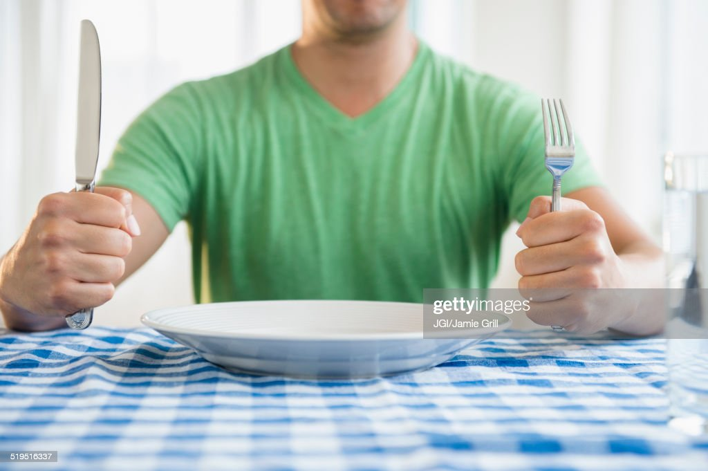 Mixed race man holding fork and knife at table : Stock Photo