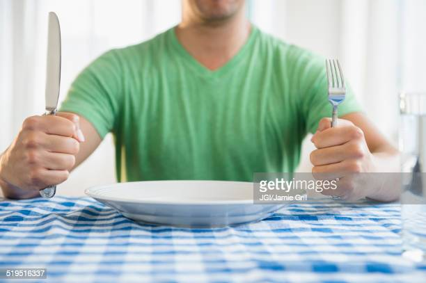 mixed race man holding fork and knife at table - hongerig stockfoto's en -beelden
