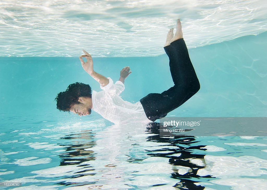 Swimming Pool Clothing : Mixed race man in clothes underwater swimming pool