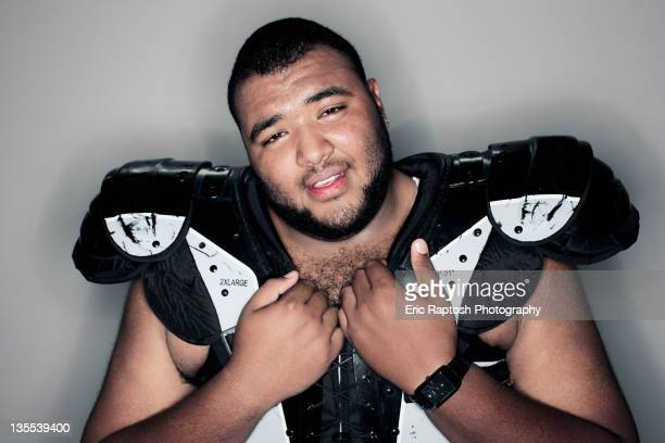 mixed race man in football shoulder pads - man with big balls stock photos and pictures