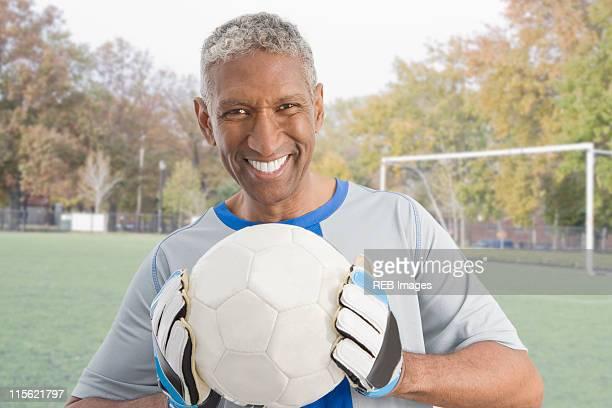 Mixed race man in soccer uniform holding ball
