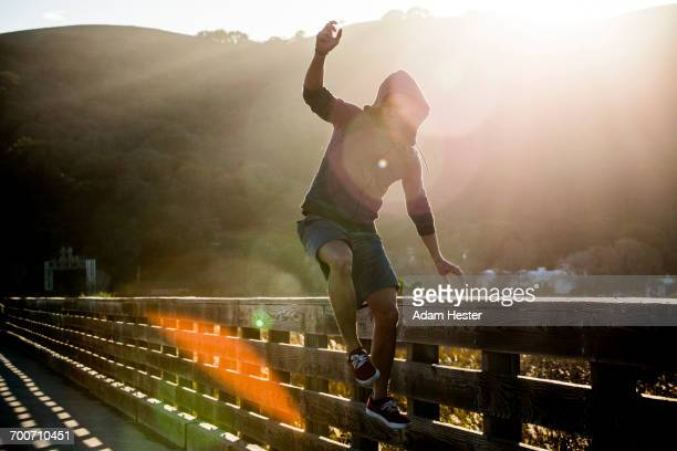 Mixed Race man jumping near railing on footbridge