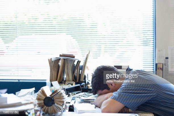 mixed race man laying on desk - jetta productions stock pictures, royalty-free photos & images