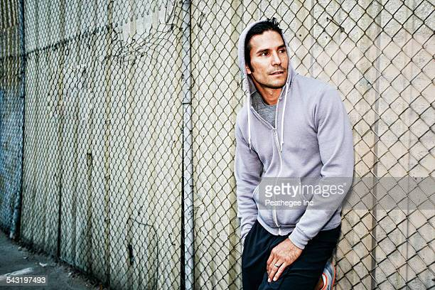 Mixed race man leaning on chain link fence