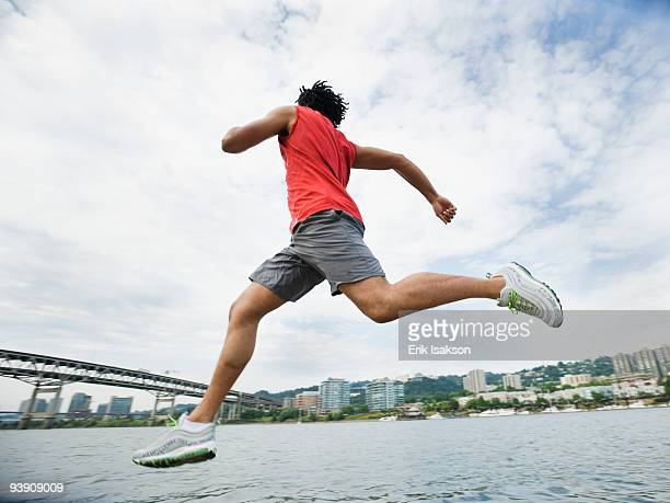 Mixed race man leaping next to river