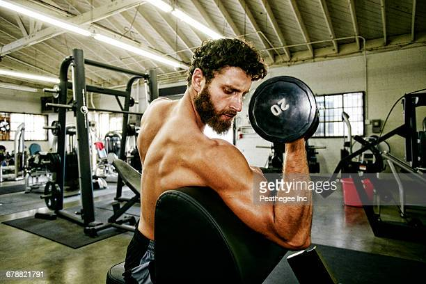 Mixed Race man lifting dumbbell in gymnasium