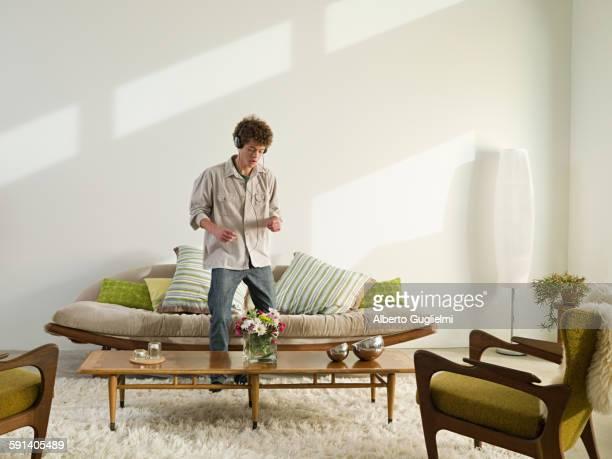 Mixed race man listening to headphones in living room
