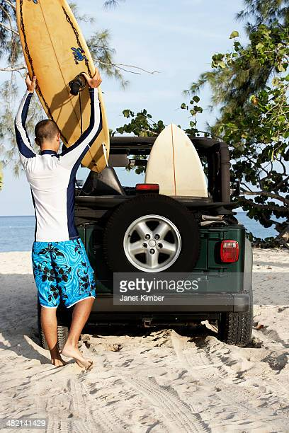 Mixed race man loading surfboards into 4x4 on beach