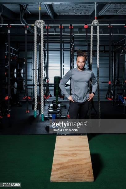 Mixed Race man looking at wooden platform in gymnasium