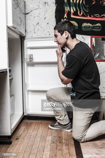 Mixed race man looking in refrigerator