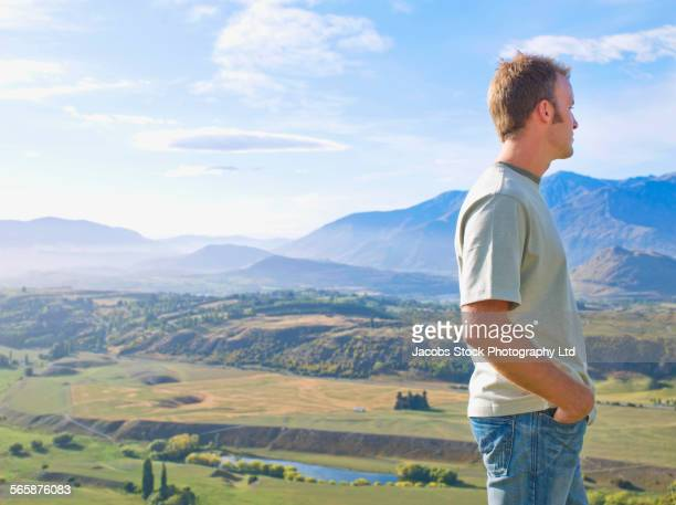 Mixed race man overlooking remote landscape, Queenstown, South Island, New Zealand