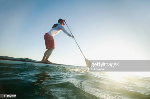 mixed race man paddling on surfboard - parte do corpo humano imagens e fotografias de stock
