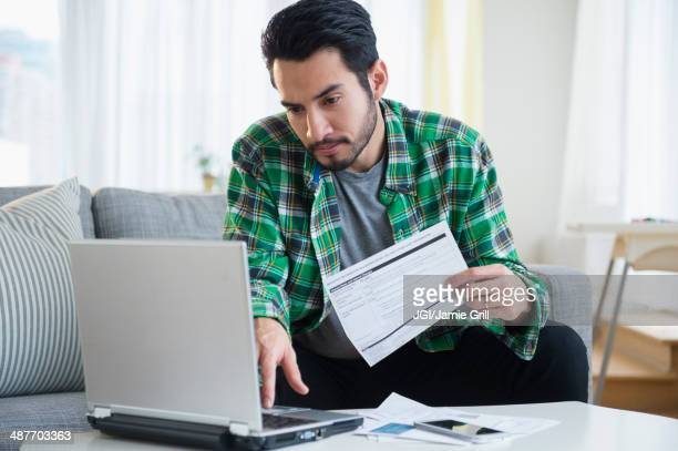 mixed race man paying bills in living room - financial bill stock pictures, royalty-free photos & images