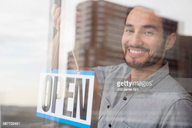 Mixed race man placing Open sign in shop window