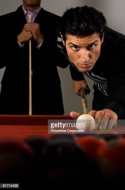 Mixed Race man playing billiards
