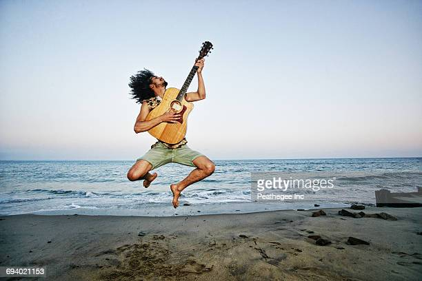 mixed race man playing guitar and jumping at beach - black shorts stock pictures, royalty-free photos & images