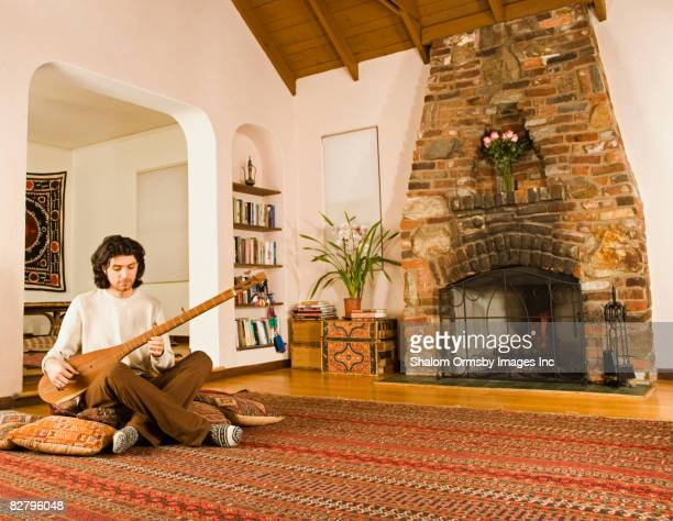 Mixed race man playing sitar on living room floor